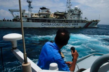 A Malaysian Navy officer makes a call as their ship approaches a Chinese Coast Guard ship in the South China Sea on March 15, 2014 in Kuantan, Malaysia.