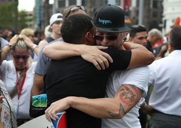 People hug as they stand together during a memorial service at the Dr. Phillips Center for the Performing Arts for the victims of the Pulse gay nightclub shooting, June 13, 2016, Orlando, Florida.