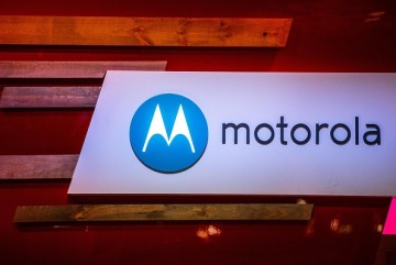 A logo sits illuminated outside the Motorola pavilion during the second day of the Mobile World Congress 2015