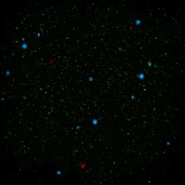The blue dots in this field of galaxies, known as the COSMOS field, show galaxies that contain supermassive black holes emitting high-energy X-rays. They were detected by NASA's Nuclear Spectroscopic Array, or NuSTAR, which spotted 32 such black holes in