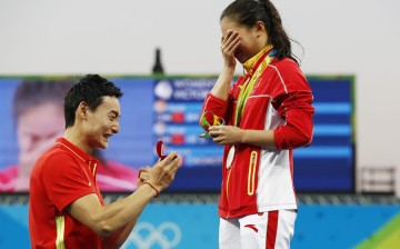 Silver medalist He Zi of China (R) receives a marriage proposal from teammate Qin Kai after the medal ceremony of the women's 3-meter springboard at the Rio Olympics on Sunday. Qin won the men's 3-meter synchronized springboard on Aug. 10.