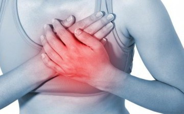 A person is seen touching her heart due to a heart disease, which is increased when a person sits for too long.