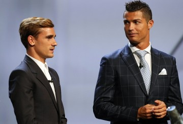 Real Madrid's Portuguese forward Cristiano Ronaldo (R) looks at Atletico Madrid's French forward Antoine Griezmann at the end of the UEFA Champions League Group stage draw ceremony.