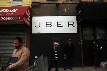 Men stand in front of a Uber sign as drivers protest the company's recent fare cuts and go on strike in front of the car service's New York offices.