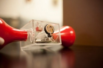 Researchers modified a hand-crank flashlight by installing a small supercapacitor (in the center) in a conventional button battery case. The light continued to glow long after the cranking stopped, th