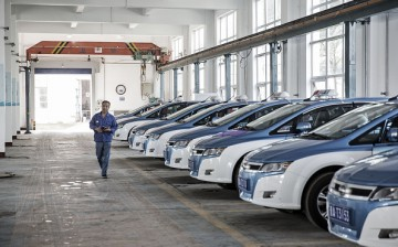 A man walks past a fleet of BYD Co. electric taxis in a charging station in Taiyuan, Shanxi Province.