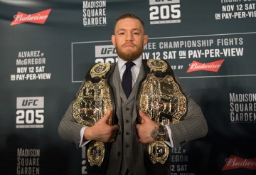 UFC two-division champion Conor McGregor holds both his belts during a press conference for UFC 205.