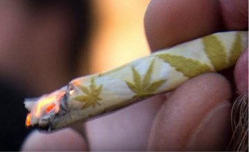 A hand-rolled marijuana cigarette with design is being smoked by a cannabis user.