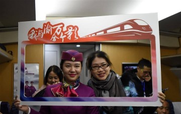 A passenger poses for a group photo with a train attendant on a train running on Chongqing-Wanzhou high-speed railway, southwest China, Nov. 28, 2016.