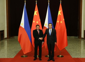 Philippine President Rodrigo Duterte (L) shakes hands with Chinese Premier Li Keqiang (R).