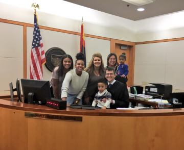Michael Brown poses for a photo with his new family and the judge that finalised his adoption last Dec. 20.