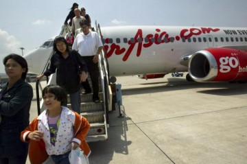 Travellers are seen disembarking from the Air Asia Boeing 737-300 flight from Bangkok to Phuket on February 25, 2004 in Phuket, Thailand.
