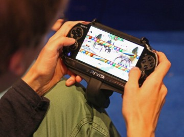 A gaming enthusiast tries out a Sony Playstation Vita game at the Gamescom 2013 gaming trade air on August 22, 2013 in Cologne, Germany.