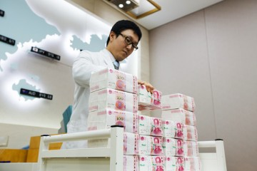 An employee piles bundles of yuan notes in an offshore bank.