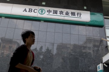 A man walks past the Agricultural Bank of China Ltd., the nation's third-largest lender by market value, as government cracks down on lending to curb loan expansion.