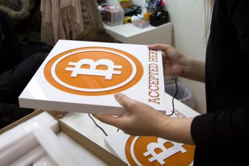 A worker holds a sign at the first bitcoin retail store to open in Hong Kong on Feb. 28, 2014.
