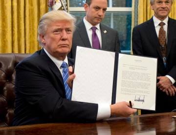 U.S. President Donald Trump shows the Executive Order withdrawing the U.S. from the Trans-Pacific Partnership (TPP) after signing it in the Oval Office of the White House on Monday, Jan. 23, 2017.