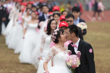 Couples participate in a group wedding ceremony.