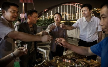 Chinese men toast each other while drinking thier locally made wine called baijiu at dinner on the Chishui River, on Sept. 23, 2016 in Maotai, Guizhou Province, China.