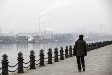 A man strolls along a waterfront boardwalk facing factories and a shipbuilding yard in Dalian, China.