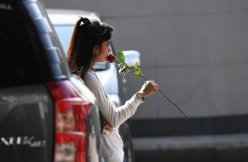 A young woman holds a rose as she waits in a parking area.