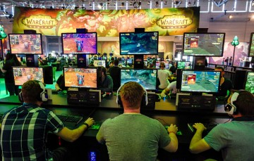 Visitors try out the massively multiplayer online role-playing game 'World Of Warcraft' at the Blizzard Entertainment stand at the Gamescom 2016 gaming trade fair during the media day on August 17, 2016 in Cologne, Germany.