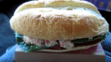 A McDonald's crab sandwich is placed on top its packaging for display.