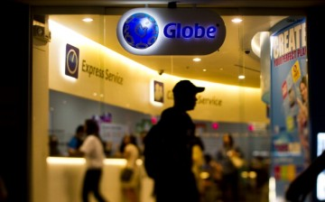 Shoppers try out mobile devices at a Globe Telecom Inc. retail outlet in Manila, Philippines.