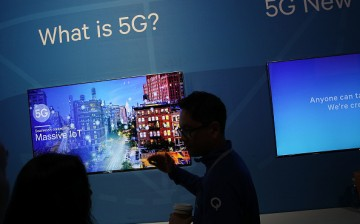 An attendee listens to information about 5G, aka 5th generation mobile networks, at the Qualcomm booth during CES 2017.