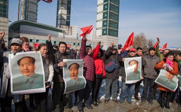 Residents hold posters of late communist leader Mao Zedong during a protest calling for a boycott of South Korean goods in Jilin, in China's northeast Jilin Province on March 5, 2017.