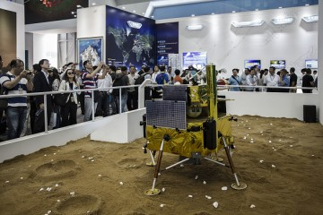 Visitors walk past a model of a Chinese lunar lander at the China International Aviation & Aerospace Exhibition in Zhuhai, China.