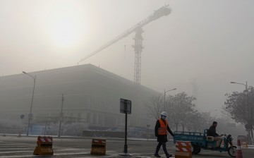 A construction worker walks in the smog in Beijing, China.