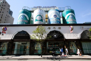 Pedestrians walk outside Tsingtao Brewery in Qingdao Beer Street in the town of Qingdao, Shandong Province.