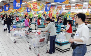 Chinese shoppers stand at the check-out counters inside a Carrefour supermarket store in the Gubei district of Shanghai.