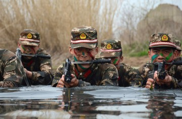 Armed Chinese commandos train in water on March 30, 2016 in Chuzhou, Anhui Province of China.