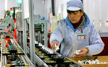 Chinese employees working on an energy-saving bulb production line at a lighting factory in Suining, southwest China's Sichuan Province.