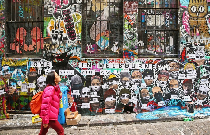People walk past walls adorned with graffiti in Hosier Lane.