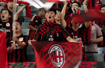 Chinese fans of the AC Milan soccer team sing during a friendly match in Shenzhen, Guangdong province.