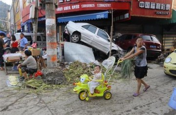 A woman pushes a baby on bike next to damaged cars and debris in Beijing.