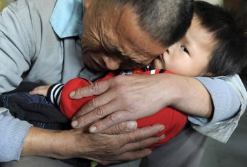 Wang Bangyin, a local farmer, holds his rescued son after the pair were reunited at Guiyang Welfare Centre for Children in Guiyang, Guizhou Province, Oct. 29, 2009.