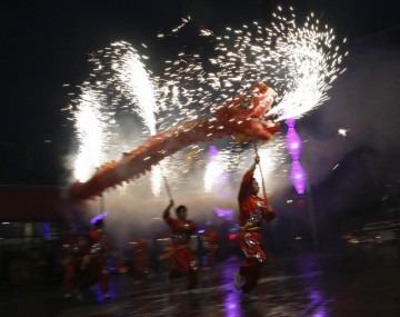 A dragon mascot sets off firecrackers during the advent of the Year of the Sheep.