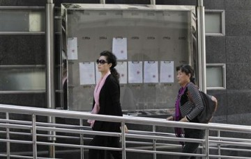 Singer Meng Ge (L) walks into court ahead of a verdict hearing for her son in Beijing, Sept. 26, 2013.