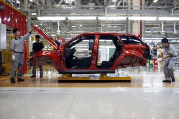 Employees work at the production line inside the Chery Jaguar Land Rover plant before the plant's opening ceremony in Changshu, Jiangsu Province.
