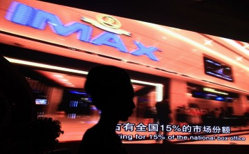 A model stands in front of a video presentation before the start of an official signing ceremony between Wanda Group and AMC Entertainment in Beijing.