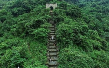 An aerial shot of the Hailongtun in Guizhou Province shows tourists ascending its ancient stairs.