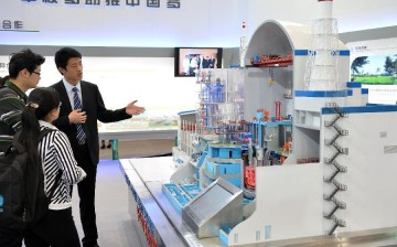 A staff member gives an introduction of the experimental fast reactor to visitors in front of a model during an exhibition in Beijing, China, April 15, 2014.