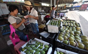 Gao Yufen (2nd L), a WeChat shop owner, bargains with a fruit vendor in Haikou, Hainan Province, on June 17, 2015. Gao is one of millions who use Wechat to bring in customers.
