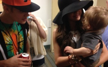 Justin Bieber and Selena Gomez relax backstage at a Phish concert on August 15, 2012 in Long Beach, California.