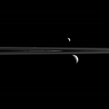 Saturn's rings along with its trio of moons, Rhea, Enceladus and Atlas.