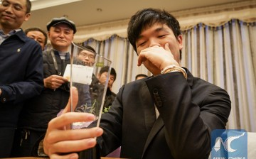 Chinese Go grandmaster Ke Jie holds his trophy after beating Lee Se-dol in the 2nd MLily Cup in this Jan. 5, 2016 photo.